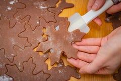 Sternförmiger Kuchen wird durch woman's Hände mit einer weißen Spachtel, die Vorbereitung für Weihnachtsgebäck angehoben stockfotografie