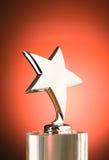Sternpreis gegen roten Hintergrund Stockfotografie
