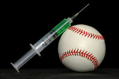 Steroids and baseball. Syringe with steroids leaning on a baseball stock photos