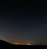 Sterren in donkere nachthemel met stadslichten op de horizon Royalty-vrije Stock Afbeeldingen