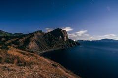 Sterrige donkerblauwe hemel, bergen en overzees in dorp van Novy Svet in de Krim Stock Afbeeldingen