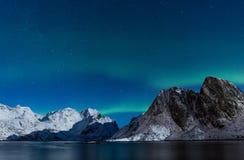 Sterrige hemel met noordelijke lichten ofer steile rotsachtige bergen in nr Stock Foto