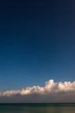 Sterrige hemel met overzees en wolken bij bodem van beeld stock foto