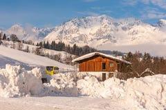 ?sterrikisk buss och tr?hus Berg p? bakgrunden Skidar regionen Schladming-Dachstein, Liezen, Styria, Österrike royaltyfria foton