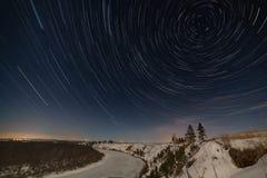 Stersleep rond de poolster in de nachthemel De winterlandschap onder de volle maan wordt gefotografeerd die stock foto