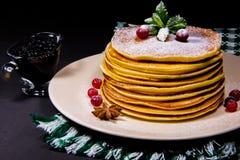 Sterta bliny na białym talerzu z zielonymi wytarcia cranberry puddingami i cynamonem kropiącymi z cukieru proszkiem along zdjęcie stock