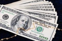Sterta 100 dolarowych rachunków i złocistej biżuteria na ciemnym tle Zdjęcia Stock