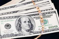 Sterta 100 dolarowych rachunków i złocistej biżuteria na zmroku - błękitny backgr Obraz Stock