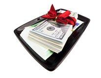 Sterta dolary & euro z prezenta faborkiem na czarnym talerzu Obraz Royalty Free
