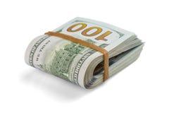 Sterta gotówkowi dolary, zginająca w połówce, pod elastycznym zespołem odizolowywa na białym tle Zakończenie obraz stock