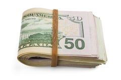 Sterta gotówkowi dolary, zginająca w połówce, pod elastycznym zespołem odizolowywa na białym tle Zakończenie obrazy stock