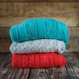 Sterta kolorowi trykotowi pulowery na drewnianym zdjęcie stock