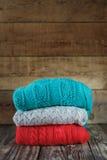 Sterta kolorowi trykotowi pulowery na drewnianym obraz stock