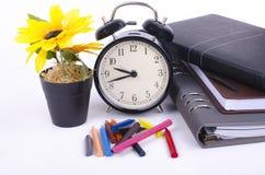 Sterta książka z cykota rocznika zegarem, sztucznego kwiatu rośliną i kolorową kredką na bielu stole, Zdjęcie Royalty Free