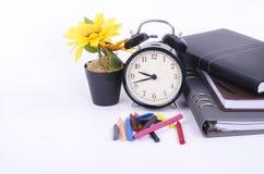 Sterta książka z cykota rocznika zegarem, sztucznego kwiatu rośliną i kolorową kredką na bielu stole, Zdjęcie Stock