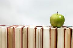 Sterta książki i jabłko na stole Obraz Stock