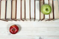 Sterta książki i jabłko na stole Obrazy Stock