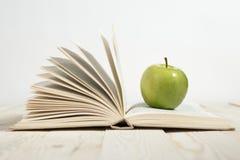 Sterta książki i jabłko na stole Obraz Royalty Free