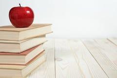 Sterta książki i jabłko na stole Zdjęcie Royalty Free