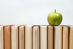 Sterta książki i jabłko na stole Zdjęcia Royalty Free