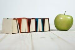 Sterta książki i jabłko na stole Zdjęcia Stock