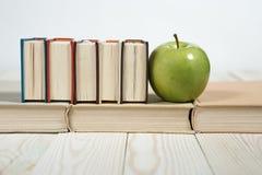 Sterta książki i jabłko na stole zdjęcie stock