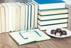 Sterta książki, otwiera książkę, szkła i czekoladowego ciastko bielu talerza, zdjęcia stock