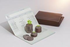 Sterta monety i obrachunkowa książka deponujemy pieniądze na stole zdjęcia stock
