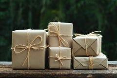 Sterta prostego eco prezenta pudełka pakunku życzliwy opakunek z brązu papierem w starym drewnianym stołowym tle, zieleni teraźni fotografia stock