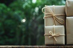 Sterta prostego eco prezenta pudełka pakunku życzliwy opakunek z brązu papierem w starym drewnianym stołowym tle, zieleni teraźni zdjęcia royalty free