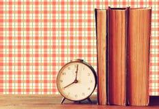 Sterta stare książki i stary zegar nad drewnianym stołem i retro stylową tapetą Fotografia Royalty Free