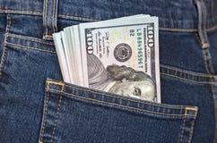 Sterta sto dolarowych rachunków w cajgach wkładać do kieszeni Fotografia Royalty Free
