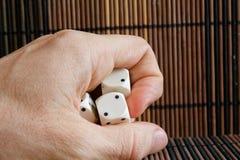 Sterta trzy biel klingeryt dices w mężczyzna ` s ręce na brown drewnianym stołowym tle Sześć stron sześcianów z czarnymi kropkami Fotografia Stock