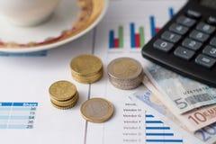 Sterty euro monety na papierowych prześcieradłach i filiżance Obrazy Royalty Free
