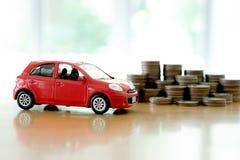 Sterty gigantyczne srebne monety obok czerwonego samochodu zdjęcie royalty free