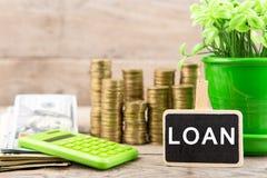Sterty monety, dolarowi rachunki, kalkulator, blackboard z tekstem i x22; LOAN& x22; zdjęcie stock