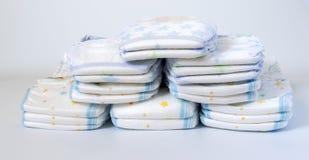 Sterty pieluszki brogować w zataczających się rzędach na białym tle Zdjęcie Stock