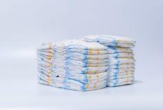 Sterty pieluszki brogować w zataczających się rzędach na białym tle Obrazy Stock