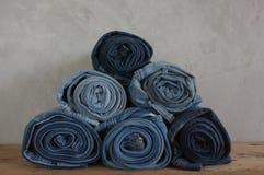 Sterty rolki błękitni drelichowi cajgi na drewnie Fotografia Stock