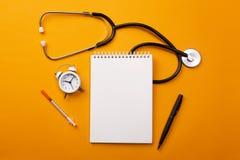 Stethoscoop in artsenbureau met notitieboekje, wekker en pillen, hoogste mening royalty-vrije stock fotografie