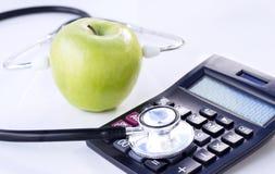 Stethoscoop, calculator en groene die appel op witte lijst wordt geïsoleerd royalty-vrije stock afbeeldingen