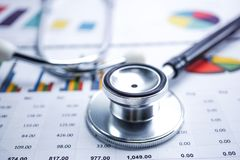 Stethoscoop en Amerikaanse dollarbankbiljetten op grafiek of millimeterpapier, Financieel, rekening, statistieken en bedrijfsgege royalty-vrije stock afbeelding