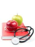 Stethoscoop en appelen op een boek stock foto