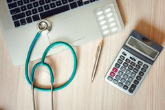 Stethoscoop en Calculator op Arts Office Table , De Desktop van de Lijstwerkruimte voor het onderzoeken van geduldige gezondheid  stock afbeelding