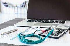 Stethoscoop en calculator op de lijst en het materiaalhulpmiddelen van het artsenbureau , De Desktop van de Lijstwerkruimte voor  stock foto