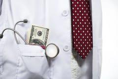 Stethoscoop en geld in de zak van de medische artsentoga stock afbeeldingen