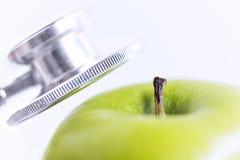 Stethoscoop en groene appel op witte achtergrond stock afbeelding