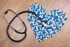 Stethoscoop en hart van blauwe tabletten, pillen of capsules wordt gemaakt die Stock Fotografie