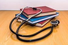 Stethoscoop en medische boeken die op een lijst liggen Stock Fotografie