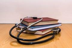Stethoscoop en medische boeken die op een lijst liggen Royalty-vrije Stock Foto's
